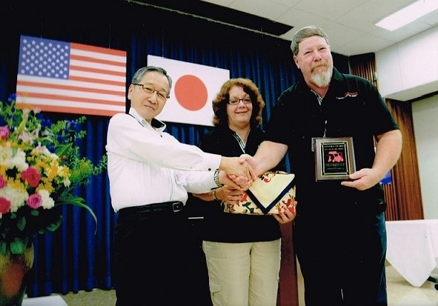 Brad (Owner and President) and Kim (Sales and Administration) Dunlap receiving the Samurai Award for outstanding Sales and Service from Mahindra in 2014
